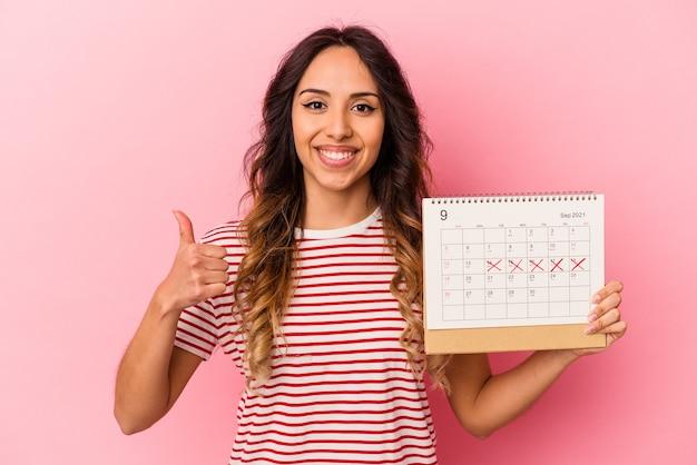 Молодая мексиканская женщина, держащая календарь на розовой стене, улыбается и поднимает большой палец вверх