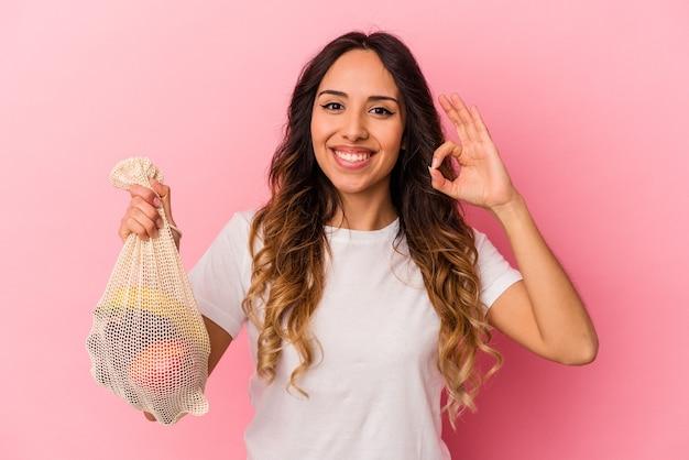 ピンクの壁に隔離されたフルーツバッグを持っている若いメキシコ人女性は、陽気で自信を持って大丈夫なジェスチャーを示しています。