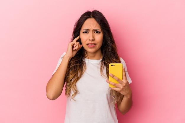 Молодая мексиканская женщина, держащая мобильный телефон, изолирована на розовом фоне, закрывая уши руками.