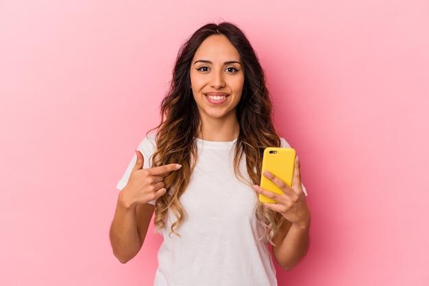 자랑스럽고 자신감, 셔츠를 손으로 가리키는 분홍색 배경 사람에 고립 된 휴대 전화를 들고 젊은 멕시코 여자