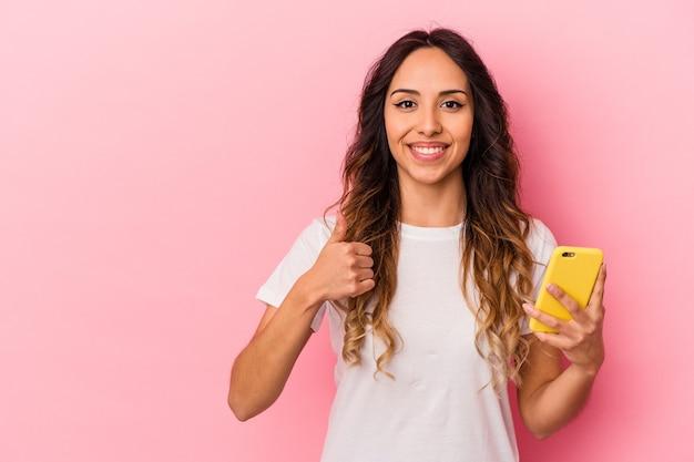 Молодая мексиканская женщина, держащая мобильный телефон на розовом фоне, улыбается и поднимает большой палец вверх