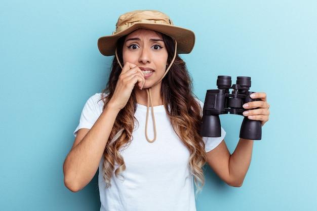 쌍안경을 들고 파란 배경에 고립되어 손톱을 물어뜯고 긴장하고 매우 불안한 젊은 멕시코 여성.