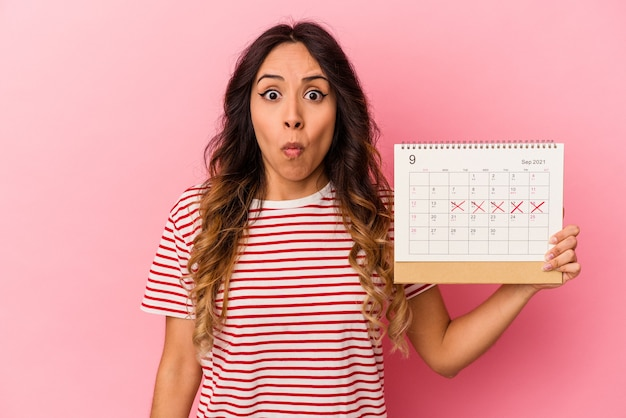 Young mexican woman holding a calendar isolated on pink background shrugs shoulders and open eyes confused.