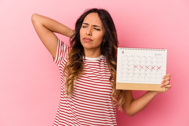Young mexican woman holding a calendar isolated on pink background touching back of head, thinking and making a choice.