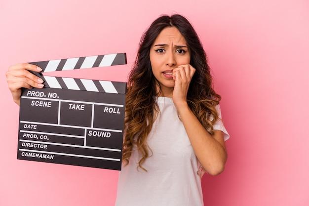 Молодая мексиканская женщина, держащая с 'хлопушкой' изолирована на розовом фоне, кусая ногти, нервничает и очень тревожится.
