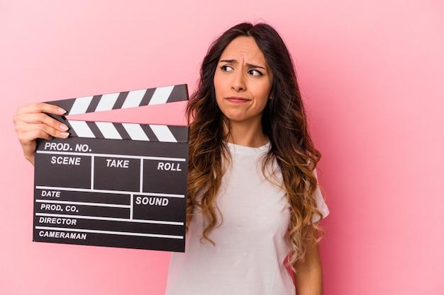 ピンクの背景にカチンコを持った若いメキシコ人女性は、混乱し、疑わしく、確信が持てません。