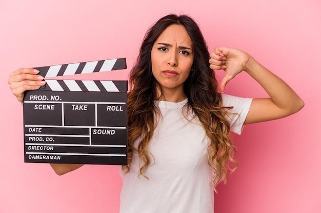 嫌いなジェスチャーを示すピンクの背景にカチンコを保持している若いメキシコ人女性は、親指を下に向けます。不一致の概念。