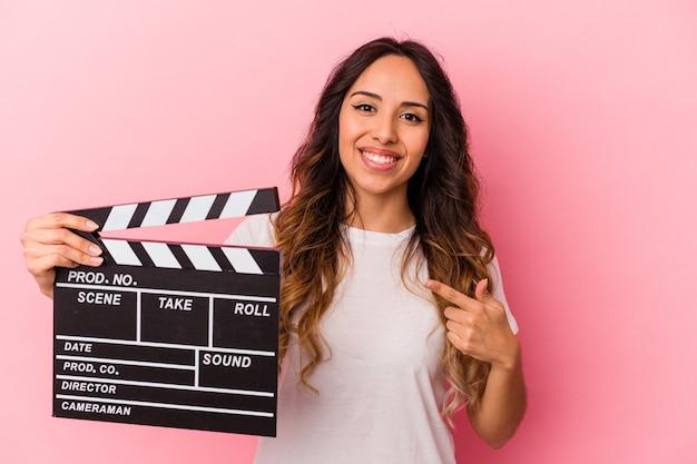 ピンクの笑顔で孤立したカチンコを持って脇を指して、空白のスペースで何かを示している若いメキシコ人女性。