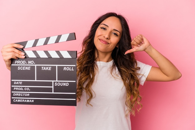 Young mexican woman holding clapperboard isolated on pink background feels proud and self confident, example to follow.