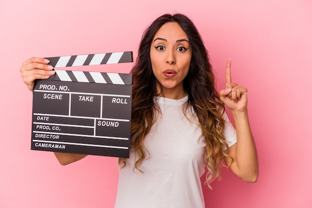 Young mexican woman holding clapperboard isolated on pink background having some great idea, concept of creativity.