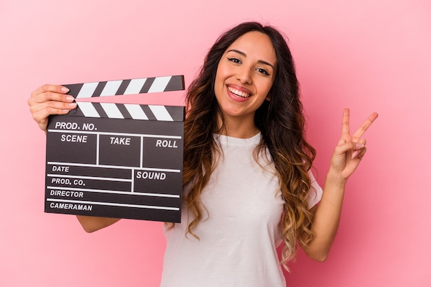 Young mexican woman holding clapperboard isolated on pink background joyful and carefree showing a peace symbol with fingers.