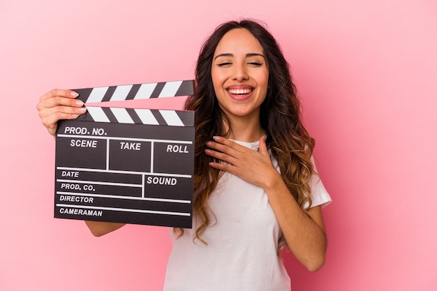 Young mexican woman holding clapperboard isolated on pink background laughs out loudly keeping hand on chest.