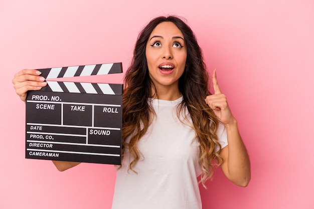 Young mexican woman holding clapperboard isolated on pink background pointing upside with opened mouth.