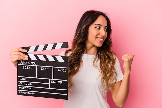 Young mexican woman holding clapperboard isolated on pink background points with thumb finger away, laughing and carefree.