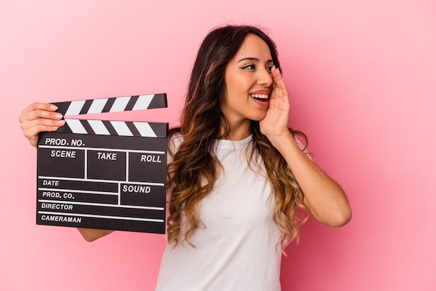 Young mexican woman holding clapperboard isolated on pink background shouting and holding palm near opened mouth.