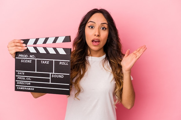 Young mexican woman holding clapperboard isolated on pink background surprised and shocked.
