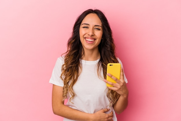 Young mexican woman holding a mobile phone isolated on pink background laughing and having fun.
