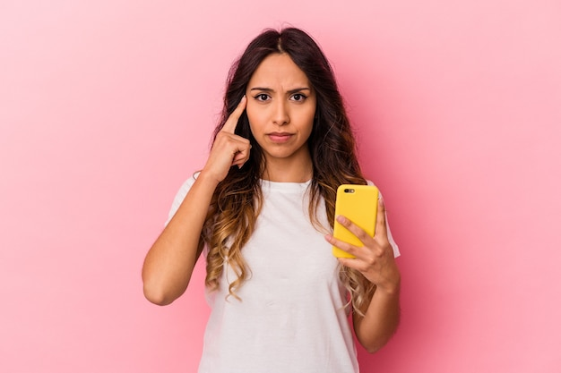 Young mexican woman holding a mobile phone isolated on pink background pointing temple with finger, thinking, focused on a task.