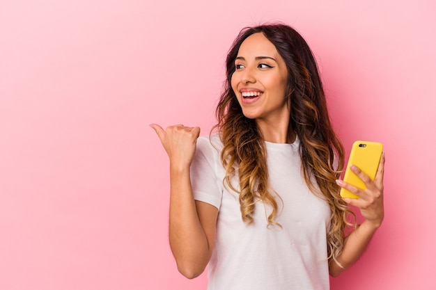 Young mexican woman holding a mobile phone isolated on pink background points with thumb finger away, laughing and carefree.