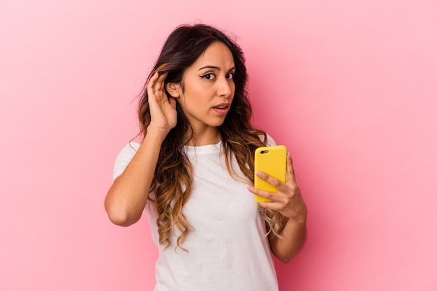 Young mexican woman holding a mobile phone isolated on pink background trying to listening a gossip.
