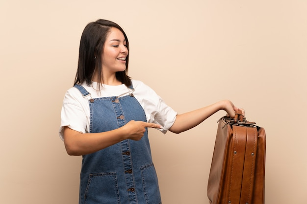 Young mexican woman   holding a vintage briefcase