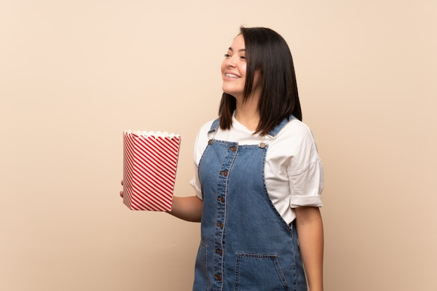 Young mexican woman over isolated background holding a bowl of popcorns