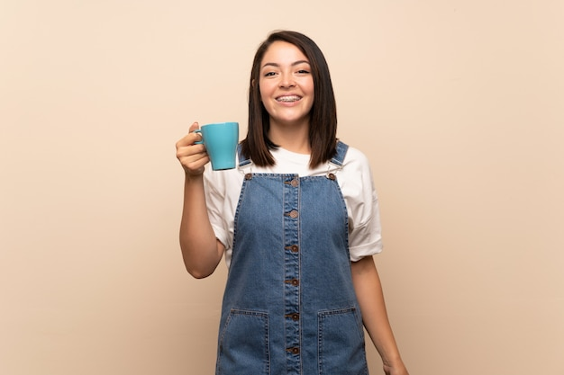 Young mexican woman over isolated background holding hot cup of coffee