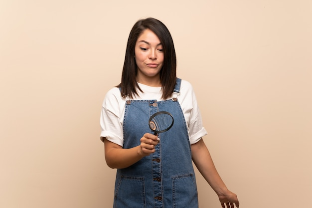 Young mexican woman over isolated background holding a magnifying glass