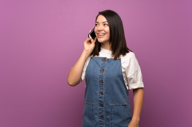 Young mexican woman over isolated background using mobile phone
