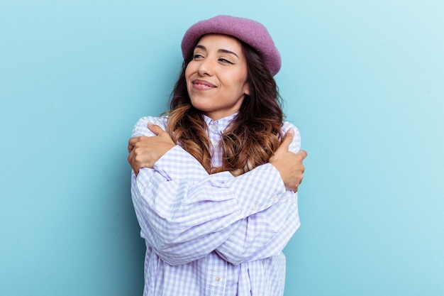 Young mexican woman isolated on blue background hugs, smiling carefree and happy.