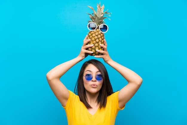 Young mexican woman over isolated blue holding a pineapple with sunglasses