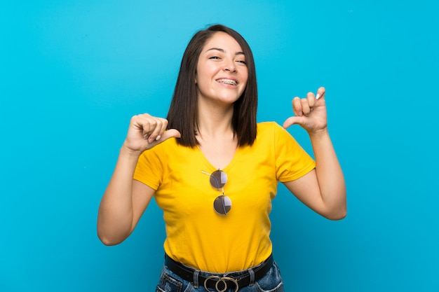 Young mexican woman over isolated blue proud and self-satisfied