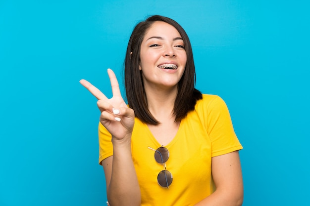 Young mexican woman over isolated blue smiling and showing victory sign