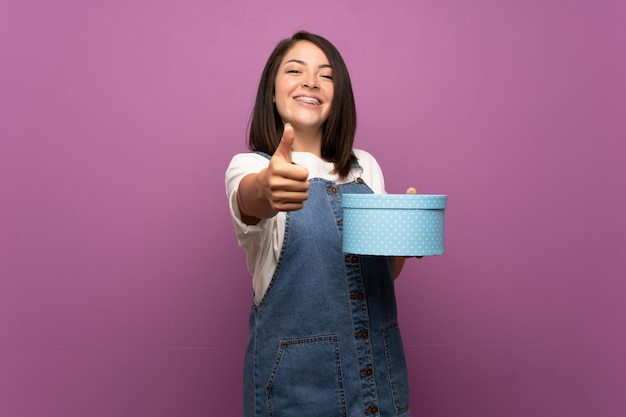 Young mexican woman over isolated holding gift box