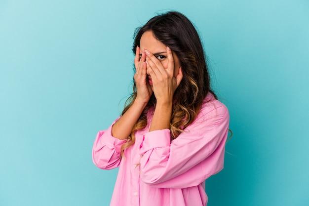 Молодая мексиканская женщина, изолированная на синем фоне, моргает сквозь пальцы испуганно и нервно.