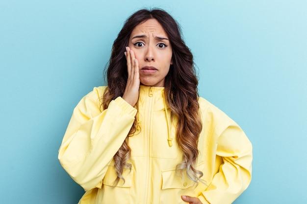 파란색 배경에 고립된 젊은 멕시코 여성은 뺨을 불고 피곤한 표정을 짓고 있습니다. 표정 개념입니다.