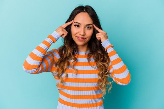 Молодая мексиканская женщина, изолированная на синем фоне, сосредоточилась на задаче, держа указательные пальцы, указывая головой.