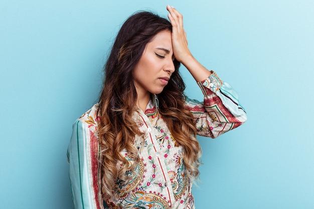 Молодая мексиканская женщина изолирована на синем фоне, что-то забывая, хлопая ладонью по лбу и закрывая глаза.