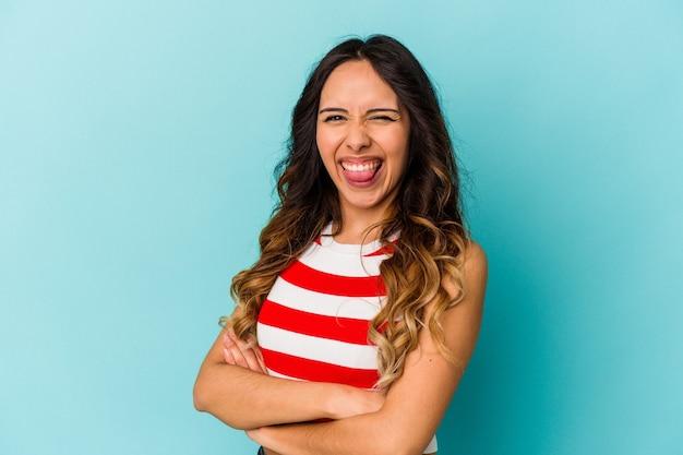 Молодая мексиканская женщина, изолированных на синем фоне, смешно и дружелюбно высунув язык.