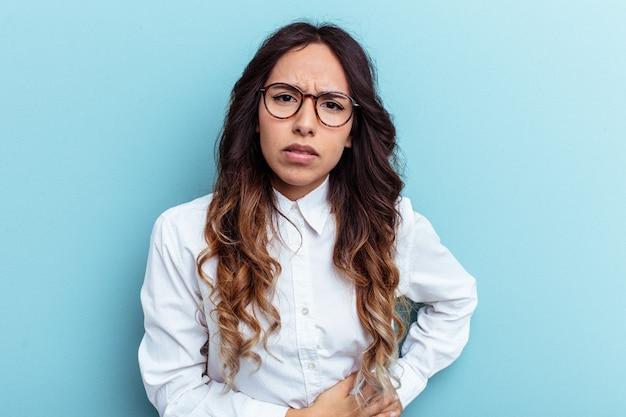 肝臓の痛み、胃の痛みを持っている青い背景で隔離の若いメキシコ人女性。