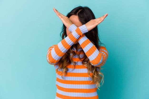 두 팔을 유지하는 파란색 배경에 고립 된 젊은 멕시코 여자 넘어, 거부 개념.