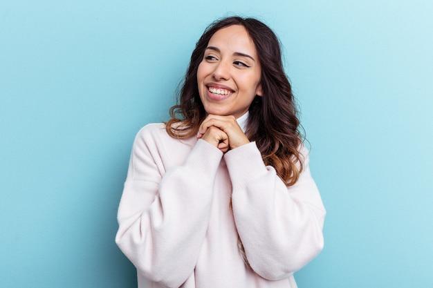 Молодая мексиканская женщина, изолированная на синем фоне, держит руки под подбородком, счастливо смотрит в сторону.