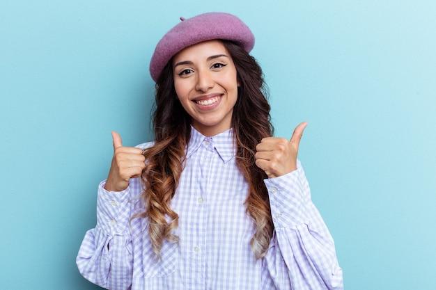 青い背景に孤立した若いメキシコ人女性は、両方の親指を上げ、笑顔で自信を持っています。