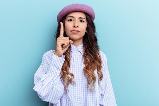 指でナンバーワンを示す青い背景に分離された若いメキシコ人女性。