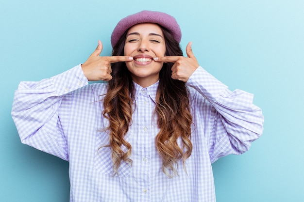 파란색 배경 미소에 고립 된 젊은 멕시코 여자 입에 손가락을 가리키는.