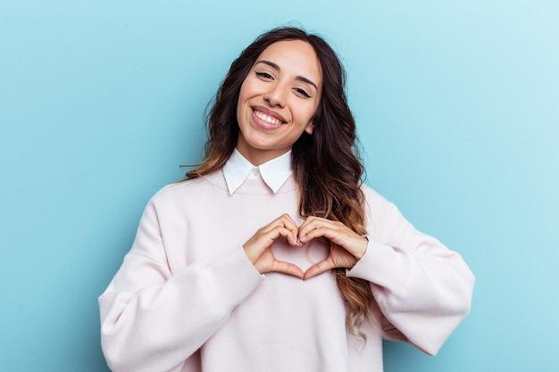 Молодая мексиканская женщина, изолированных на синем фоне улыбается и показывает форму сердца руками.