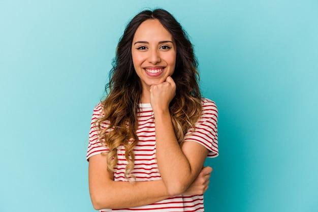 행복 하 고 자신감, 손으로 턱을 만지고 웃 고 파란색 배경에 고립 된 젊은 멕시코 여자.