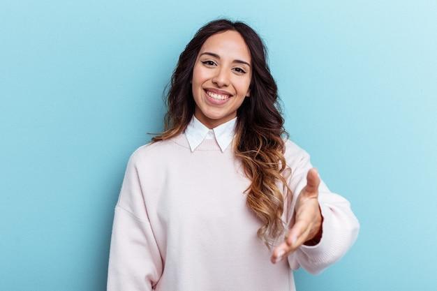 挨拶のジェスチャーでカメラに手を伸ばす青い背景に分離された若いメキシコ人女性。