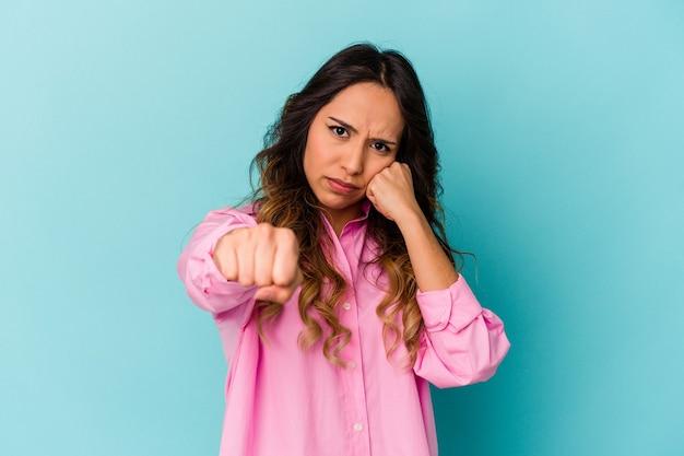 펀치, 분노, 인수, 권투로 인해 싸우는 파란색 배경에 고립 된 젊은 멕시코 여자.
