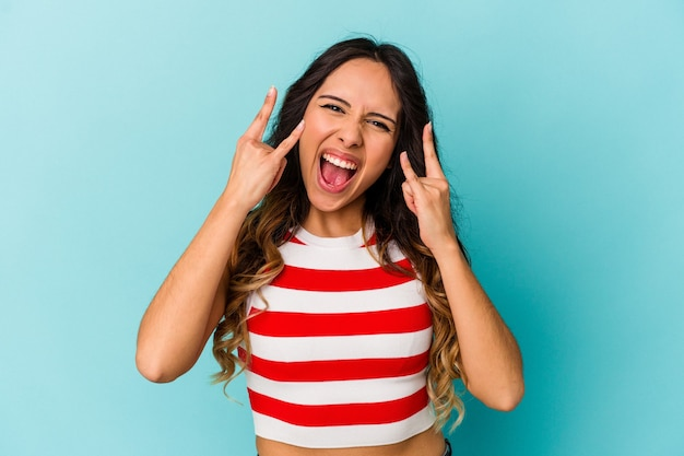 Молодая мексиканская женщина изолирована на синей стене, показывая жест рогов как концепцию революции. Premium Фотографии